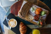 top view of table with breakfast, cappuccino coffee and french breakfast with homemade croissant and granola with fruits