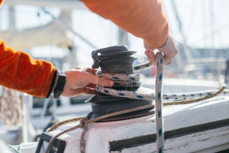 Professional sailor man ties up nautical rope on winch on boat