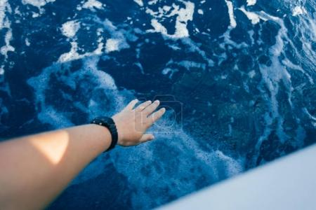 hand from yacht reaching to water