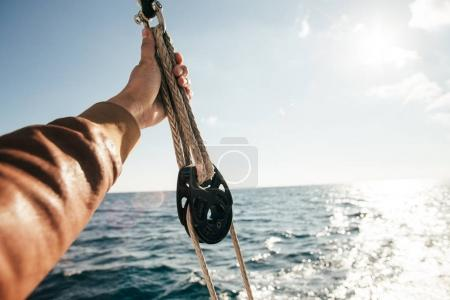 Professional sailor person hand holding rope on yacht boat during cruise in open sea