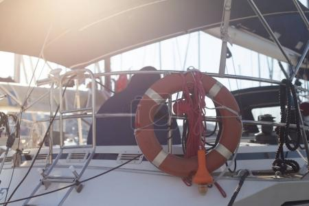 back view of marine Sailor in boat, life saving ring hanging on yacht
