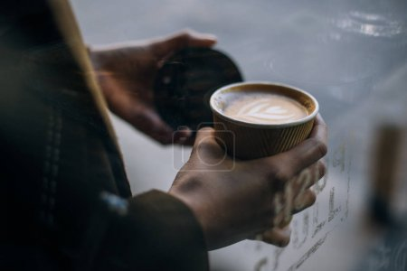 cropped view of woman holding takeaway cup with coffee to go