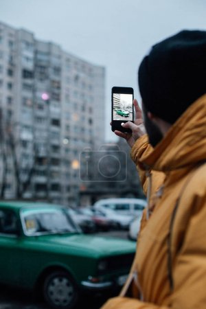 Social media influencer or mobile photographer makes photo of old vintage car on smartphone. internet and technology addiction