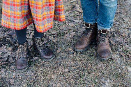 cropped view of two pairs of human legs in skirt and jeans