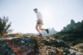 Professional trail runner, ultra distance athlete runs through rocky terrain high on mountain path or hiking trail, healthy lifestyle activity outdoors on sunny day. Active young man in sport wear