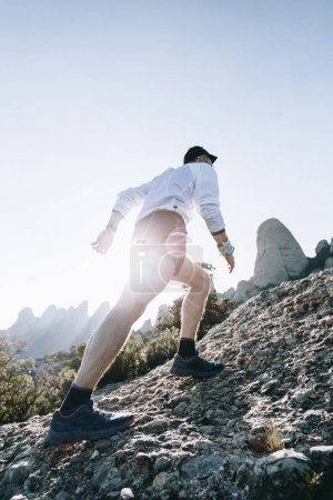 Professional athlete trail runner, climbs up steep...