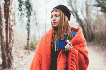 Moda hipster millennial joven mujer con el pelo rojo, acurrucado en manta de lana celebración de metal azul taza de camping con café o té, durante la aventura en el bosque, estilo de vida inspirador