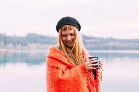 Hermosa mujer joven linda y atractiva con el pelo rojo acurrucado en manta a cuadros de color rosa o naranja, sostiene taza de camping azul con café o té, disfruta de estilo de vida al aire libre