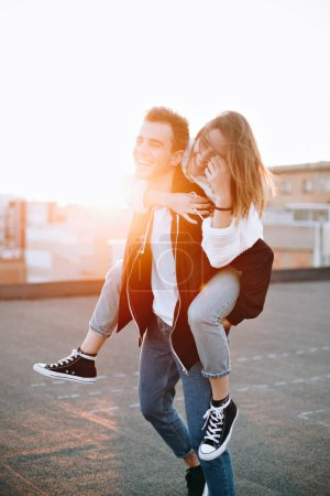 Happy and cute adorable adult couple of millennial hipsters, man with woman girlfriend on piggy back, have fun play, laugh,smile and jump on sunset at rooftop, crazy in love, emotions and relationship