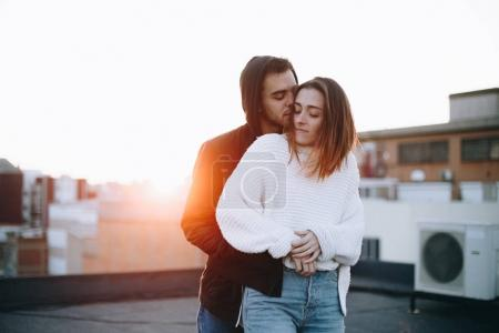 Beautiful and natural, real pretty couple of teenagers or millennials, cuddle and hug each other lovingly on top of rooftop in sunset. Inspiring relationship goals bloggers or lovers. new generation