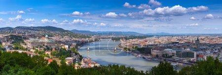 Photo pour Vue panoramique du paysage urbain de la capitale hongroise Budapest depuis la colline de Gellert. Les ponts reliant Buda et Pest à travers le Danube. Journée ensoleillée estivale, ciel bleu et vert des arbres - image libre de droit
