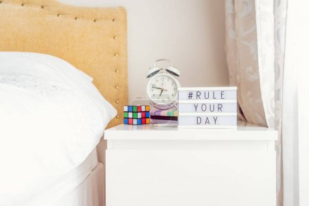 Photo for Inspiration Motivational Life Quotes hashtag Rule your day message on lightened box with alarm clock, notebooks and rubik's cube on the bedside table in the sunlight. Morning mood concept. Copy space - Royalty Free Image