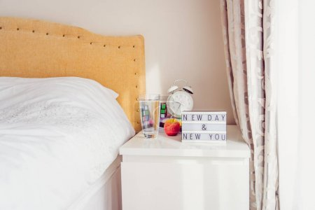 Photo for Inspiration Motivational Life Quotes New day New you message on lightened box with alarm clock, rubik's cube, notebooks on the bedside table near bed in the sunlight. Good morning mood. Copy space - Royalty Free Image