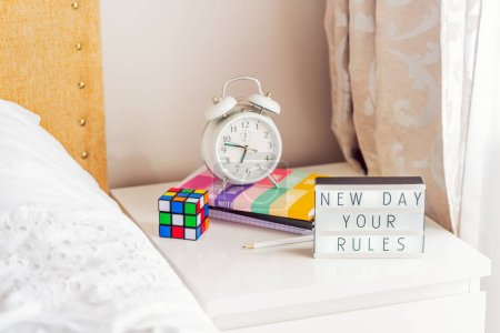 Photo for Good morning concept. Inspiration Motivational Life Quotes New day your rules message on lightened box with alarm clock, notebooks and rubik's cube on the bedside table in the sunlight. Copy space - Royalty Free Image