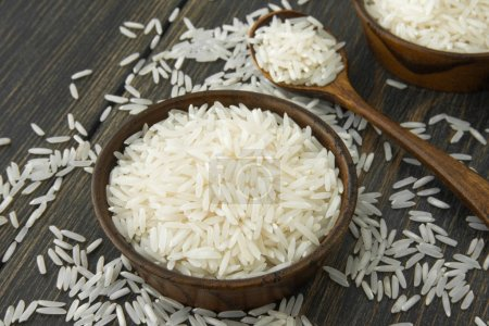 Photo for Basmati rice in small wooden bowls and spoon on black wooden background close-up - Royalty Free Image