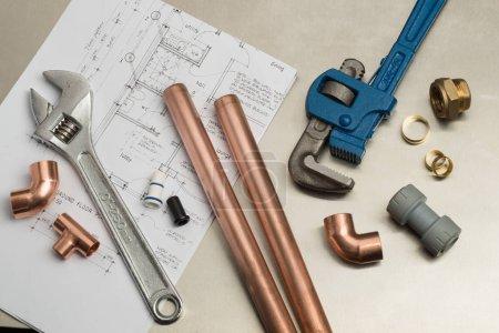 Photo pour Divers outils de plomberie et matériaux de plomberie, y compris des tuyaux en cuivre, joint de coude, clé et clé. plan de maison d'architectes sur un fond lumineux en acier inoxydable . - image libre de droit