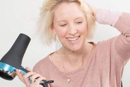 Blonde Woman Smiling While Drying Her Hair Using Blow Dryer
