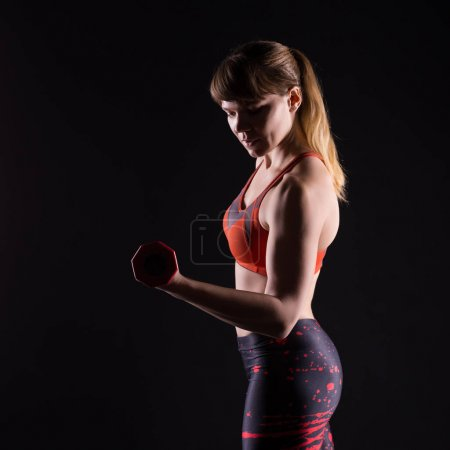 Sport woman posing in photostudio. Fitness motivation picture on dark background