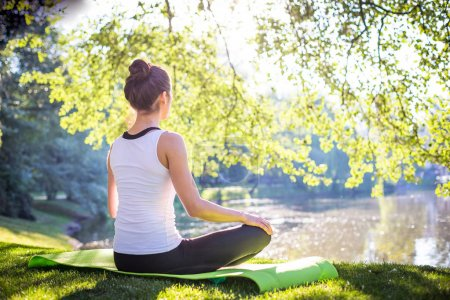 Photo for Young woman meditating while sitting on yoga carpet in morning park near lake, concept of workout at street - Royalty Free Image