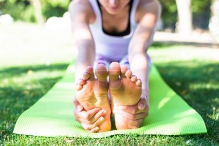 young woman doing yoga while sitting on carpet in morning park near lake