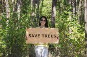 Woman in the forest holding a wooden sign with the words