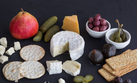 Cheese, crackers, pear, dill pickles, olives, figs and caper berries