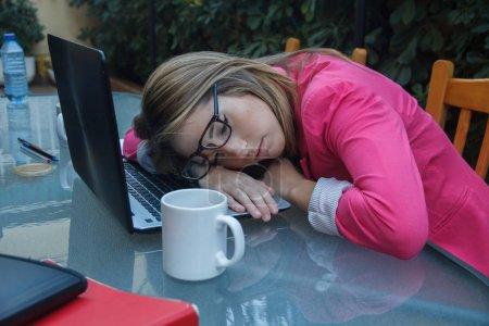 Photo pour Jeune entrepreneure fatiguée de travailler autant, elle s'endort sur le dessus de l'ordinateur portable sur la table. C'est une femme d'affaires avec trop de travail. . - image libre de droit