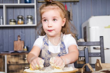 little girl cooks in the kitchen herself