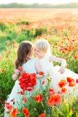 Mädchen-Modell, Hochzeit, Mohn, Sommer Modekonzept - zwei kleine Mädchen Schwestern umarmte und spielte mit Mohnblumen in weißen und blauen Brautkleider, eine Schwester hält einen Blumenstrauß von Mohn