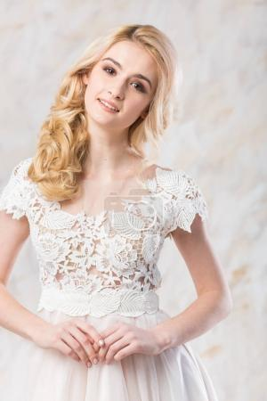 fashionable wedding dress, beautiful blonde model, bride hairstyle and makeup concept - young smiling woman in white gown indoors on light background, luxury female posing in the studio.