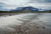 Wide and soft mountain river with rapids.