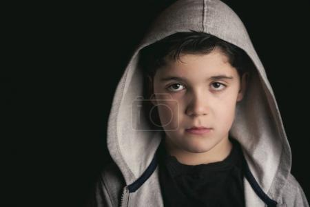 Sad boy on black background