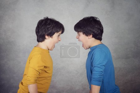 Angry children shouting over on gray background...