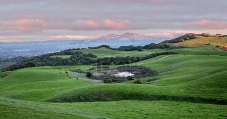 Закат над поросшему травой холмы