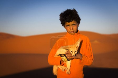 Berber child holding a desert fox poses in the Erg Chebbi dunes in Morocco.