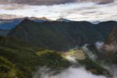 View of Machu Picchu surrounded by clouds from the Sun Gate, in Peru