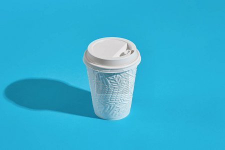 Photo for Hot coffee in white winter paper cup with lid on blue background with shadow, blurred and soft focus image. Still life. Copy space - Royalty Free Image
