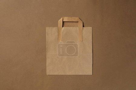 Photo pour Vaisselle jetable écologique. Le sac en papier d'artisanat biodégradable est sur fond brun. Concept de recyclage. Également utilisé dans la restauration rapide, les restaurants, les mets à emporter et les pique-niques. Gros plan. Vue en haut. Table des matières. - image libre de droit