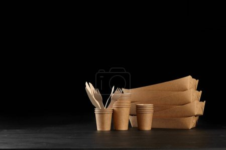Photo for Eco friendly disposable ware. Biodegradable, brown colored craft dishes, such as six containers, some folded different sized cups and bamboo wooden cutlery are standing on a dark surface against a black background. Recycling concept. Also used in fas - Royalty Free Image