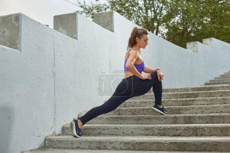 Photo pour Charmant athlète de jeune fille avec une queue de cheval, vêtu de jambières bleues, espadrilles et dessus violet s'étire le matin. Fitness modèle s'entraîne à l'extérieur dans la ville sur un escalier entouré d'arbres verts. Vue latérale. Mode de vie actif sain. Sport a - image libre de droit