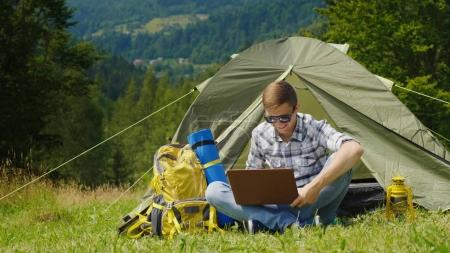 Photo for A young male tourist uses a laptop in a camping near a tent. In a picturesque place in the background of the mountains. - Royalty Free Image