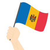 Hand holding and raising the national flag of Moldova