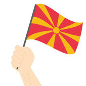 Hand holding and raising the national flag of Macedonia