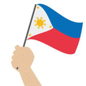 Hand holding and raising the national flag of Philippines