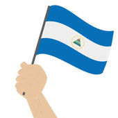 Hand holding and raising the national flag of Nicaragua