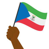 Hand holding and raising the national flag of Equatorial Guinea