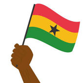 Hand holding and raising the national flag of Ghana