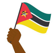 Hand holding and raising the national flag of Mozambique