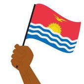 Hand holding and raising the national flag of Kiribati