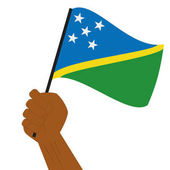 Hand holding and raising the national flag of Solomon Islands